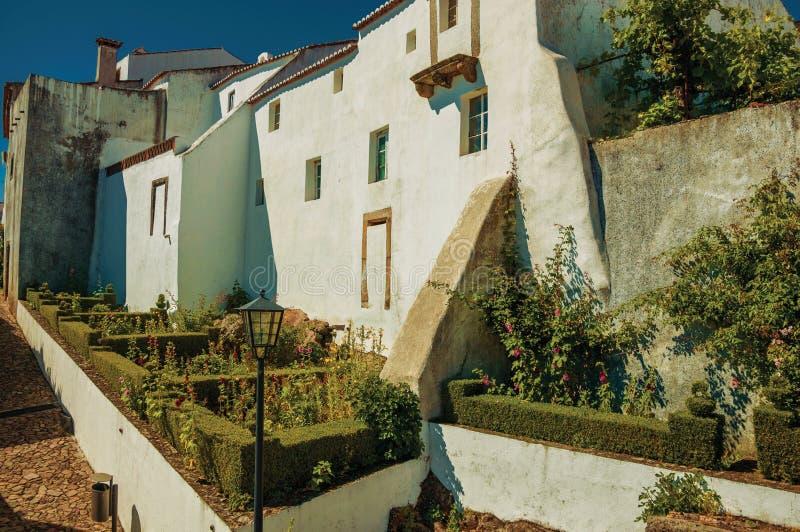Obfitolistny żywopłot i krzaki w kwitnącym ogródzie za starymi domami obraz stock