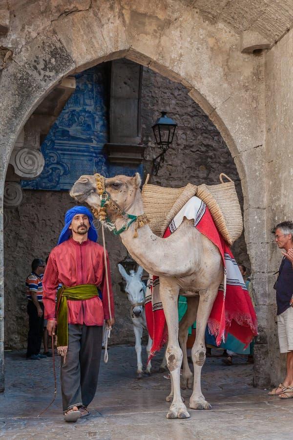 Obidos; Il Portogallo Uomo di moresco con il cammello del dromedario nella parata della rievocazione medievale del mercato immagine stock