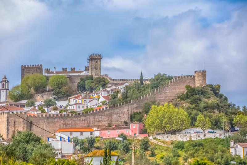 """View of the fortress and Luso Roman castle of Ã""""bidos, with buildings of Portuguese vernacular architecture and sky with clouds,. Obidos / Leiria / Portugal royalty free stock image"""