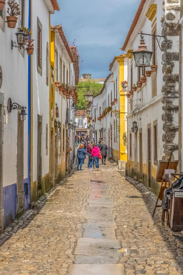 """View of a portuguese street with buildings and tourist people, on Portuguese medieval village of Ã""""bidos, in Portugal stock images"""
