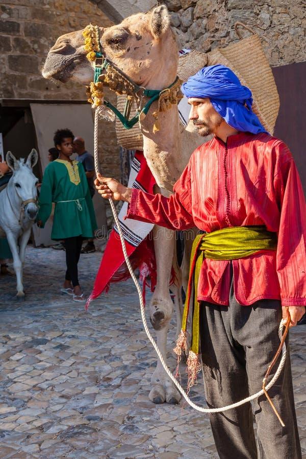 Obidos, Portugal. Moorish man with dromedary camel in the parade of the Medieval Market reenactment royalty free stock photos