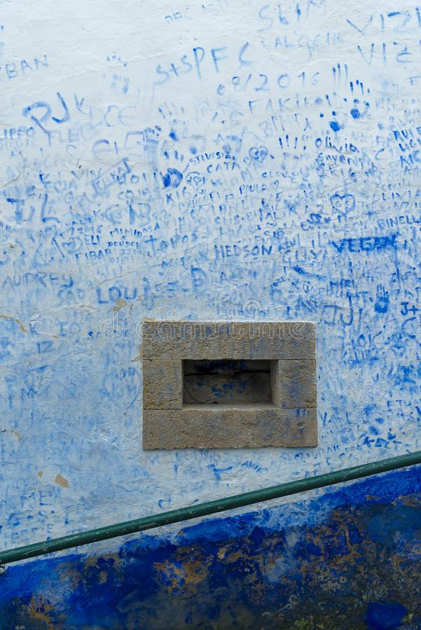Wall covered with blue graffiti stock photos