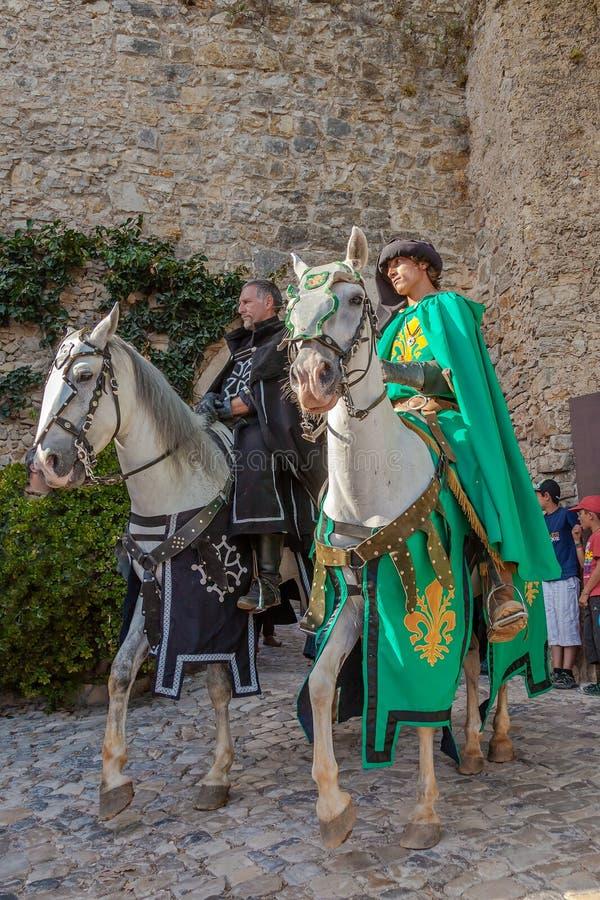 obidos portugal Riddare som rider vita hästar i ståta av den medeltida marknadsreenactmenten arkivbilder