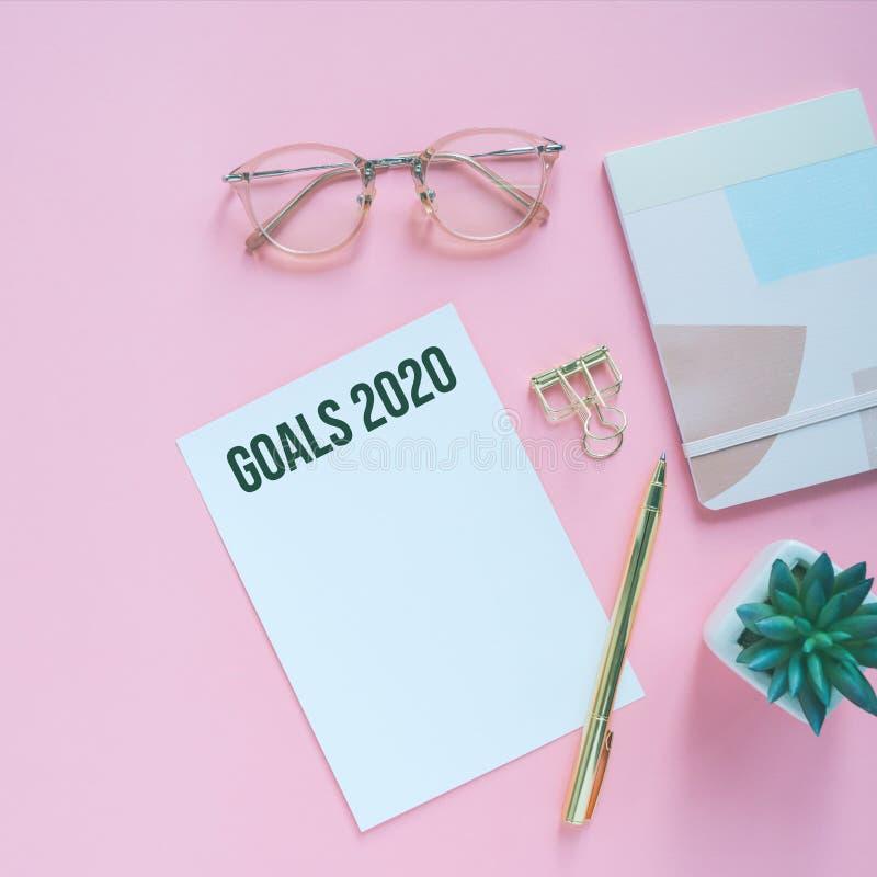 Obiettivi 2020 su un profilo piatto, foto di una scrivania colorata con scheda, occhiali e notebook con fondo spazio-copia fotografia stock libera da diritti