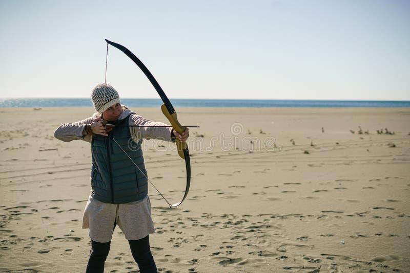 Obiettivo della fucilazione della donna con il suoi arco e freccia un giorno soleggiato sulla spiaggia immagine stock libera da diritti