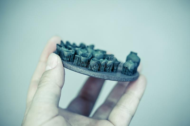 Object printed on metal 3d printer after heat treatment synteriz. Man holding object printed on metal 3d printer after heat treatment synterization close-up royalty free stock photo