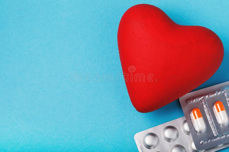 An object in the shape of a heart and pills on a blue table stock photos