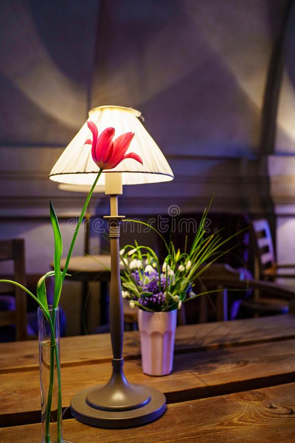 Interior cafe with desk lamp with sconces and red tulip in glass vase and small bouquet of flowers on wooden table royalty free stock photo