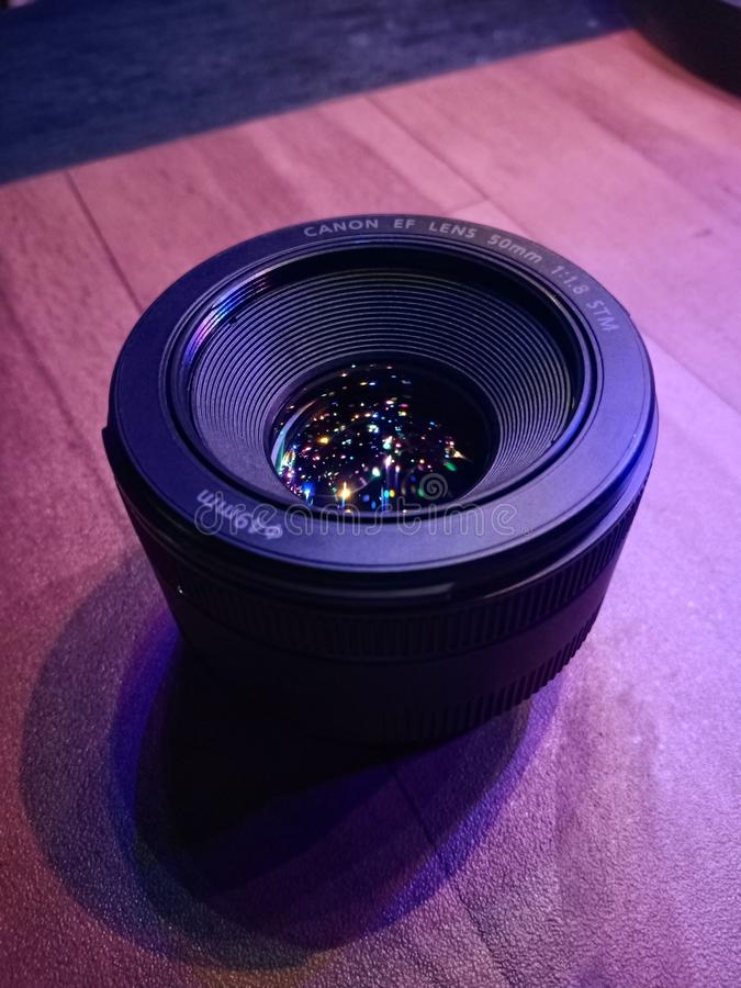 Objectif de caméra de canon avec la réflexion de la lumière shrimmering s'étendant sur la table image libre de droits