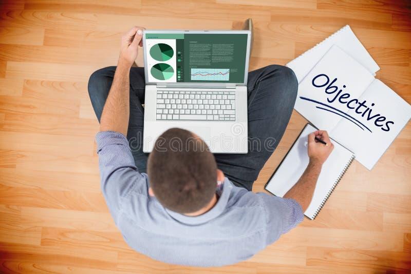 Objectifs contre le jeune homme d'affaires créatif travaillant sur l'ordinateur portable image libre de droits