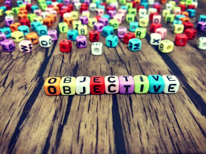 OBJECTIVE word of colourful cube alphabets. OBJECTIVE word of colourful cube alphabets on wooden background. Business concept royalty free stock images