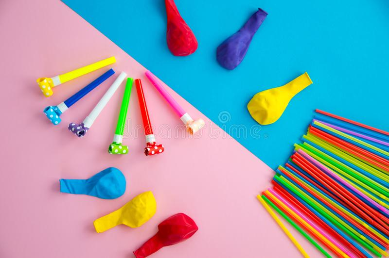 Objects for celebrating a birthday lie on a blue and pink background. Balloons, tubes for cocktails and pipes, whistles and royalty free stock images
