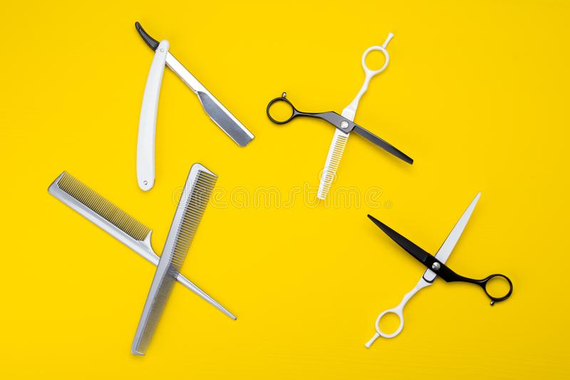 Objects for cutting hair and beard, razors and scissors, comb, lie on a yellow wooden background. royalty free stock photography