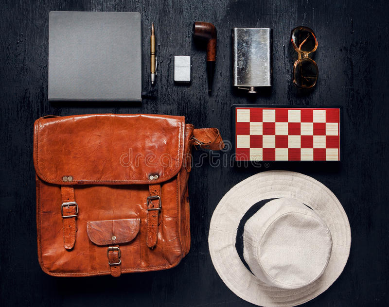 Objects in touristic set ready for a holiday. Leather travel bag, flask, notebook, smoking pipe. stock image