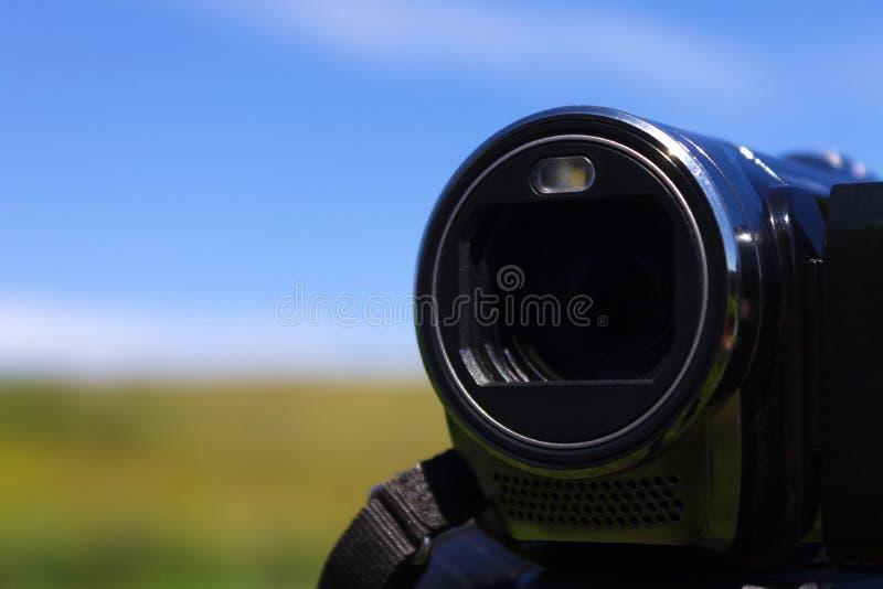 Objetiva durante o tiro na perspectiva de um campo verde e de um céu azul imagens de stock royalty free