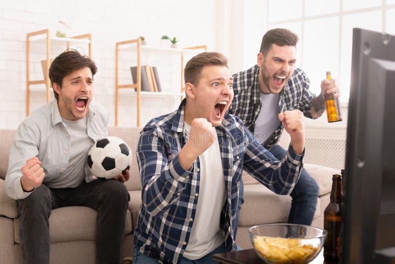 objetivo Amigos muito entusiasmados que olham o fósforo de futebol foto de stock