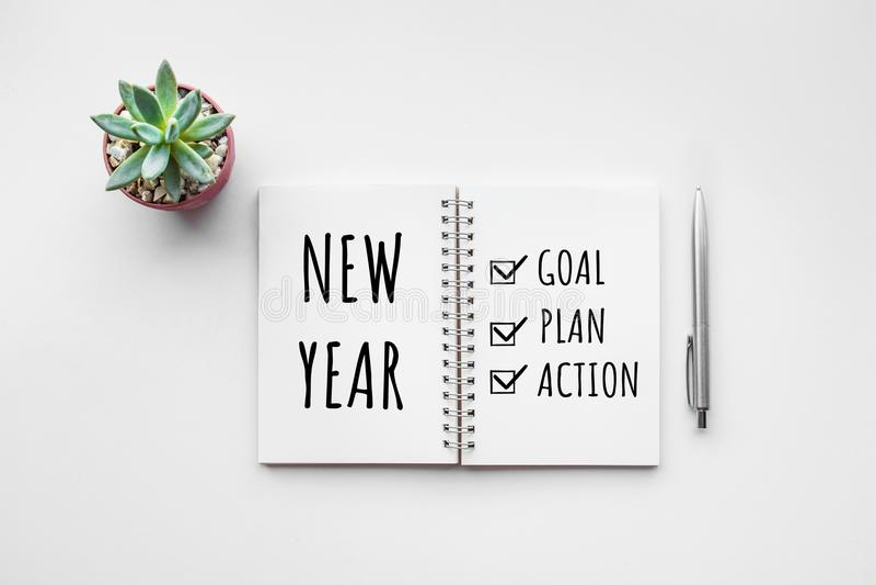 Objetivo do ano novo, plano, texto da ação no bloco de notas com acessórios do escritório fotografia de stock royalty free