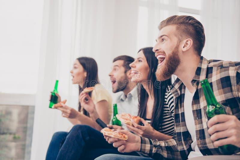 Objetivo! A juventude muito entusiasmado está tendo o divertimento olhando o matc do futebol fotos de stock royalty free