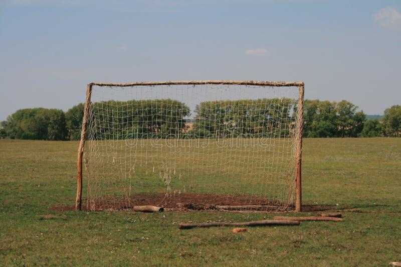 Objetivo velho do futebol para o mini futebol no gramado pisado na zona da floresta imagem de stock