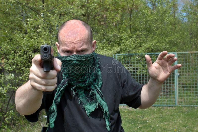 Objetivos enmascarados del hombre con el arma fotografía de archivo