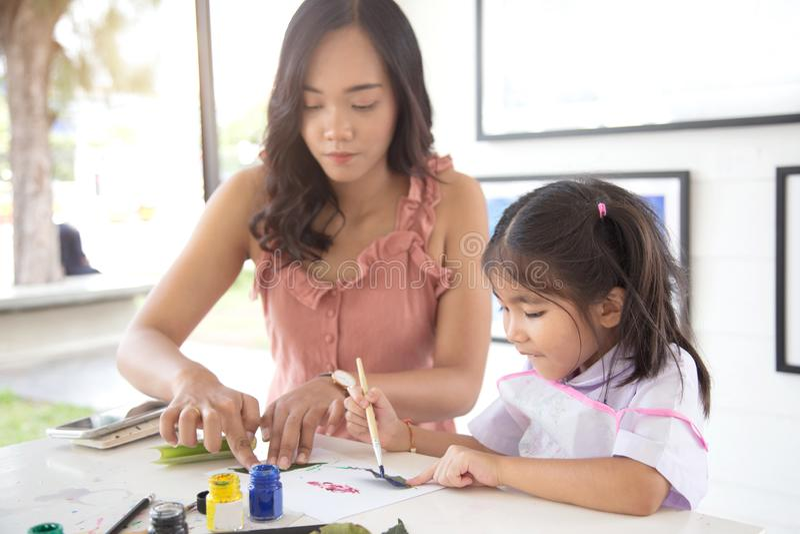 Objeto asiático feliz del arte de la madre de la familia y del funcionamiento del daugther foto de archivo libre de regalías
