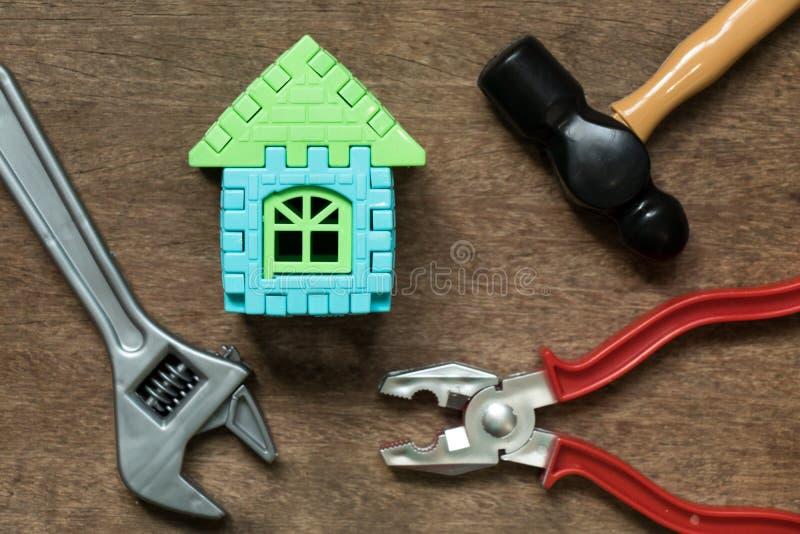 Objeto modelo da casa com a ferramenta do equipamento do brinquedo no fundo de madeira imagens de stock royalty free