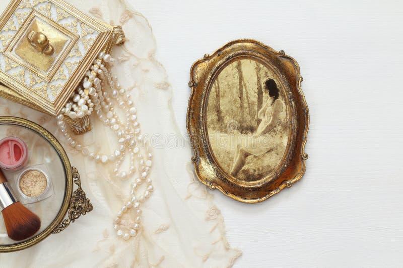 Objetos do toalete da mulher do vintage ao lado da fotografia velha imagens de stock