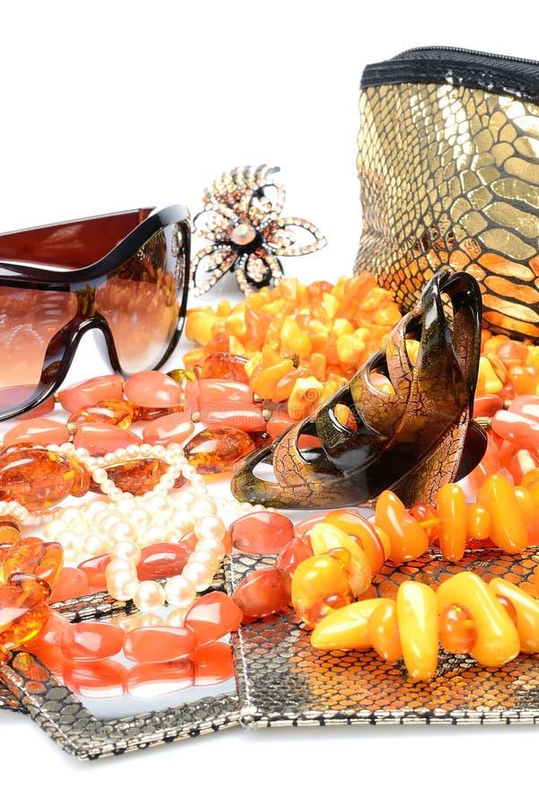 Objetos nos acessórios das mulheres do fundo e nos ornamento brancos do joalheiro - grânulos ambarinos, gancho de cabelo, óculos  imagem de stock