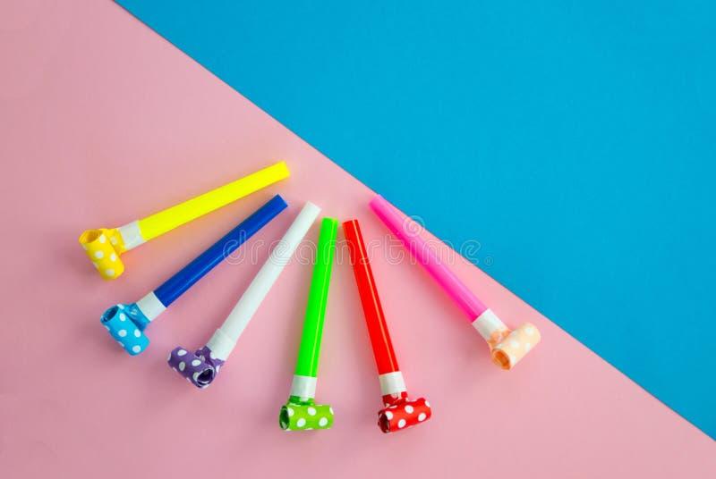 Objetos para celebrar una mentira del cumplea?os en un fondo azul y rosado Globos, tubos para los c?cteles y tubos, silbidos y foto de archivo