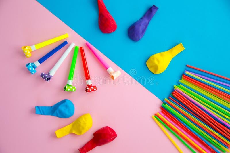 Objetos para comemorar uma mentira do aniversário em um fundo azul e cor-de-rosa Balões, tubos para cocktail e tubulações, assobi imagens de stock royalty free