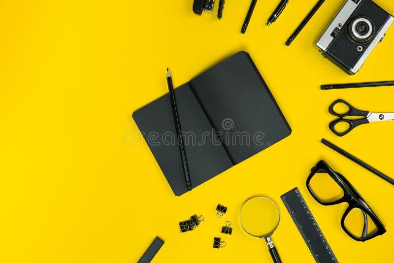 Objets noirs du bureau sur un fond jaune Travail et créativité Vue supérieure images stock