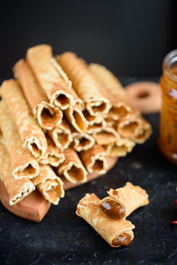 Oblatenrollen, geschmackvoll und wohlriechend, mit gekochter Kondensmilch auf einer schwarzen Tabelle stockfotos