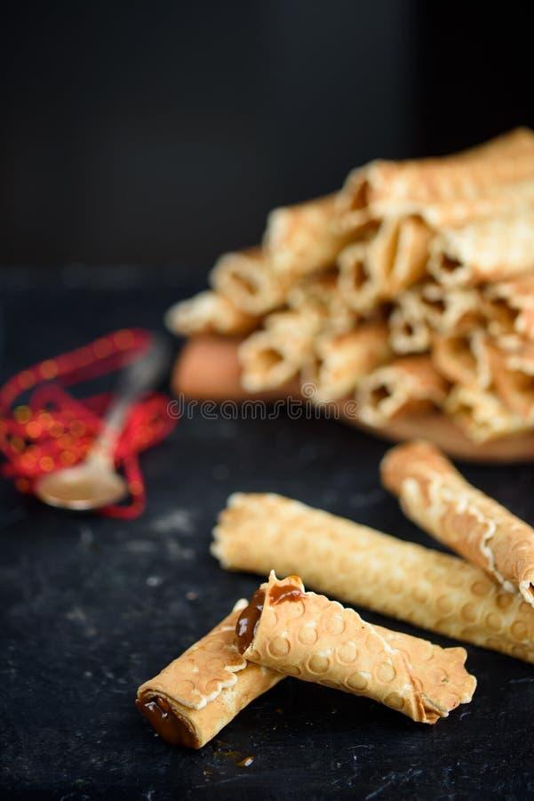 Oblatenrollen, geschmackvoll und wohlriechend, mit gekochter Kondensmilch auf einer schwarzen Tabelle stockfotografie