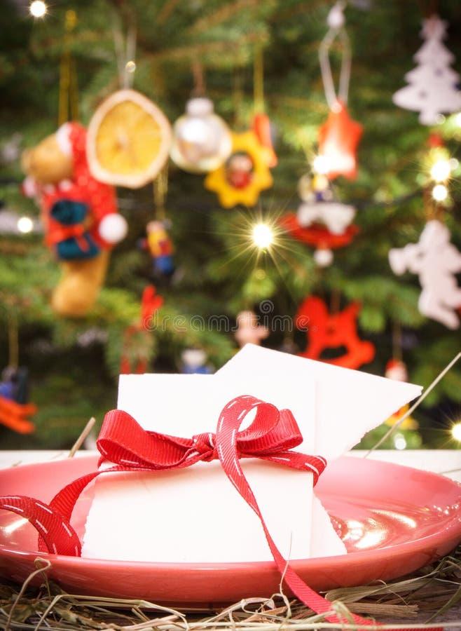 Oblea tradicional de la Nochebuena en la placa y el árbol de navidad con las luces y la decoración, concepto festivo del tiempo foto de archivo libre de regalías