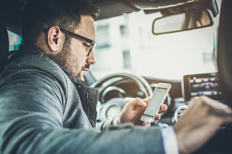 Obligation are followed by successful people. Young business man reading messages and sitting in car. Close up stock image