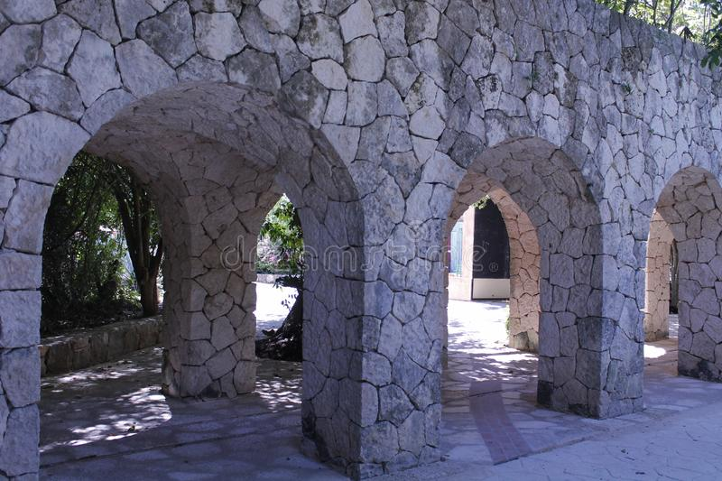 Stone arches of an aqueduct. Obliged to pass under this aqueduct across the arches of stone in Xcaret, Mexico.   Under this aqueduct there is a hallway stock image