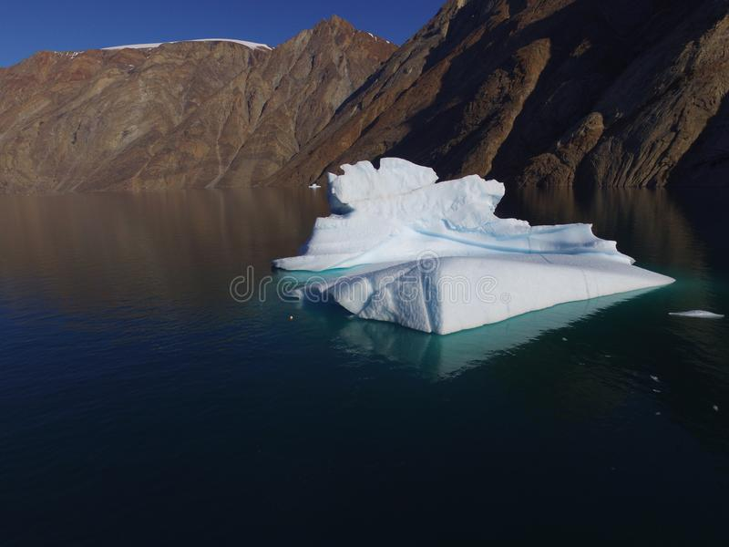 Oblique drone image of a melting iceberg in a calm fjord with mountains in the background royalty free stock photography