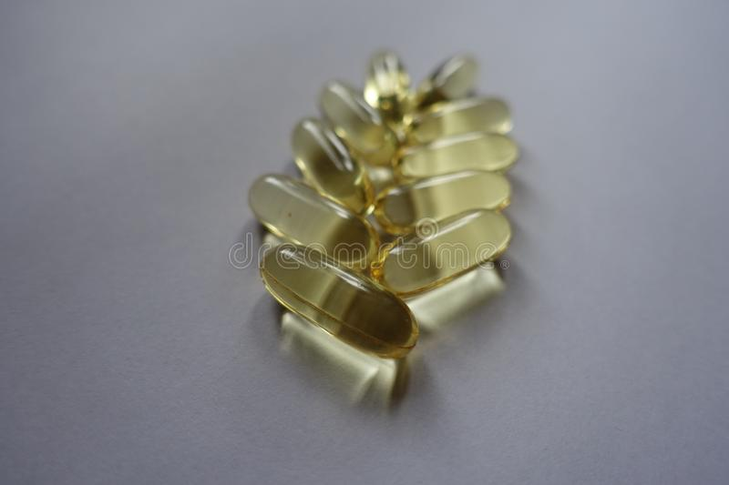 Oblong capsules of fish oil in a shape of spike stock image