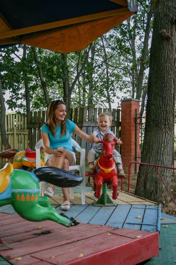 2010 08 15, Obninsk, Rusland Een moeder en een kleine jongen die op een carrousel paard en het lachen spinnen stock afbeeldingen