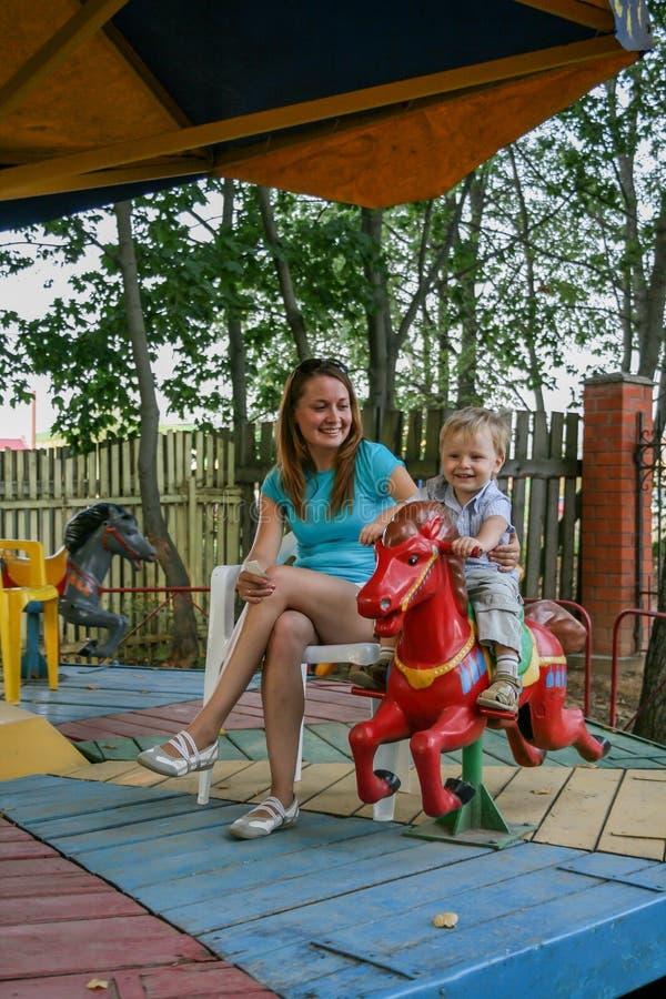 2010 08 15, Obninsk, Rusland Een moeder en een kleine jongen die op een carrousel paard en het lachen spinnen royalty-vrije stock afbeelding