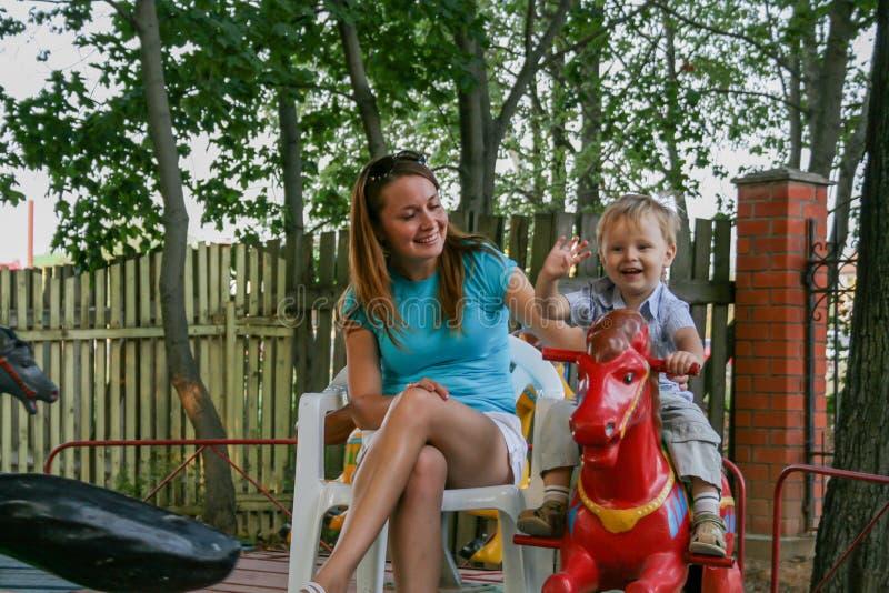 2010 08 15, Obninsk, Rusland Een moeder en een kleine jongen die op een carrousel paard en het lachen spinnen stock fotografie