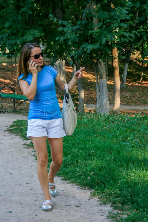2010 08 15, Obninsk, Rusland Jonge vrouw die in de het park en het spreken telefoon lopen stock foto