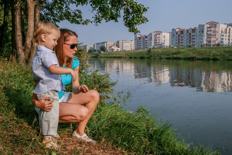 2010 08 15, Obninsk, Rusland Moeder en zoonszitting op het gras bij de rivierbank stock afbeelding