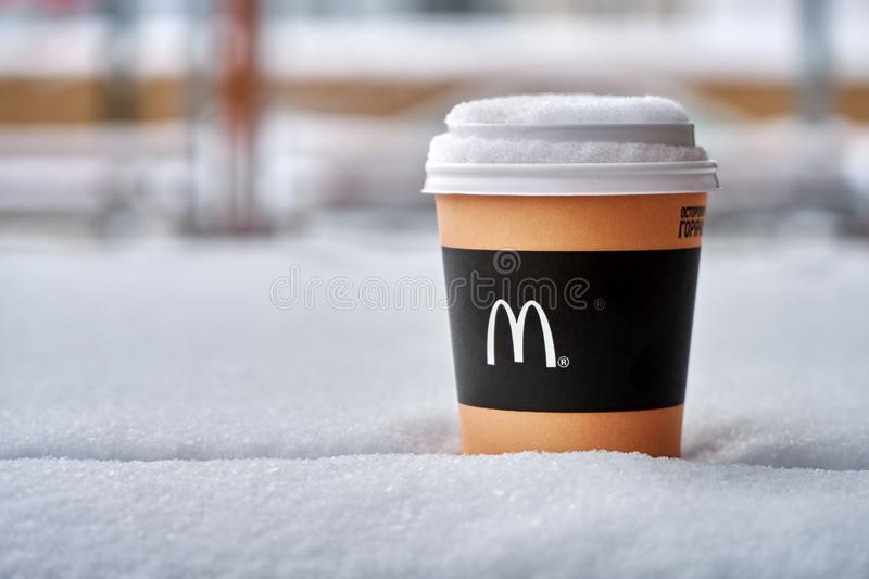 Obninsk, Russia - January 4,2019. Mcdonald`s paper cup of coffee standing on the table covered with snow stock photography
