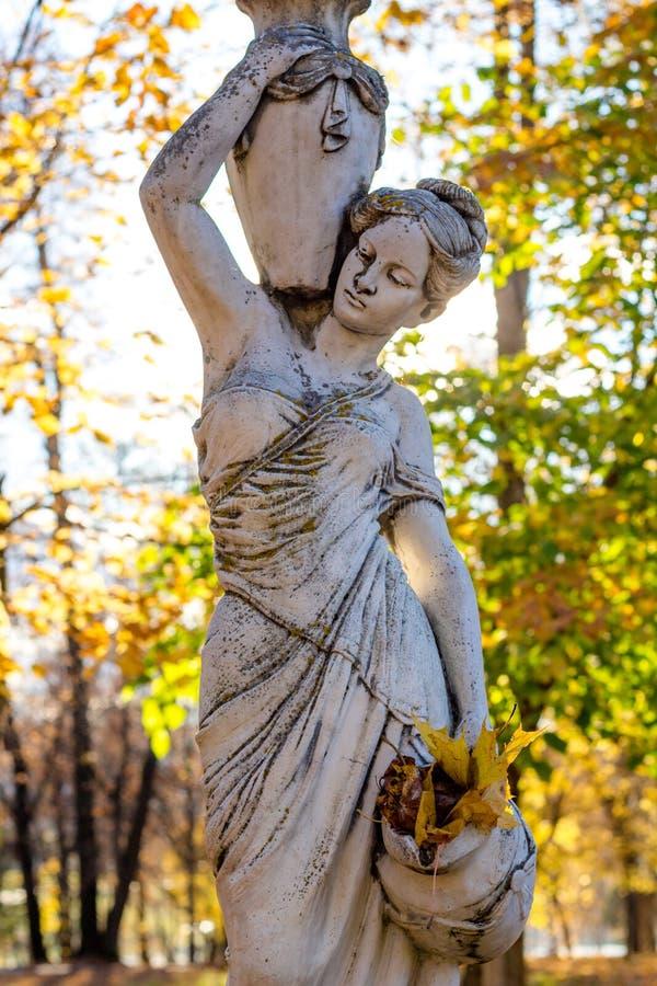 Obninsk, Russland - Oktober 2017: Parkskulptur einer Frau in der antiken Art mit Krügen und unter Herbstlaub lizenzfreies stockfoto