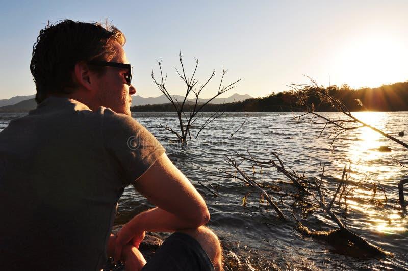 Obok jeziora cicho młodego człowieka obsiadanie fotografia stock