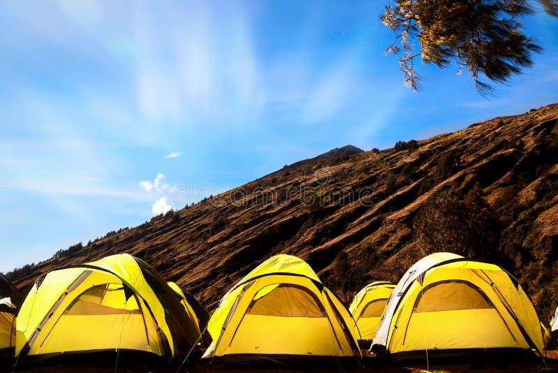 Obozowisko w górach Wiele żółci namioty przeciw niebieskiemu niebu zdjęcia royalty free