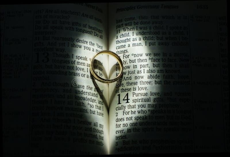 Obrączka ślubna w biblii otaczającej serca światłem obrazy royalty free