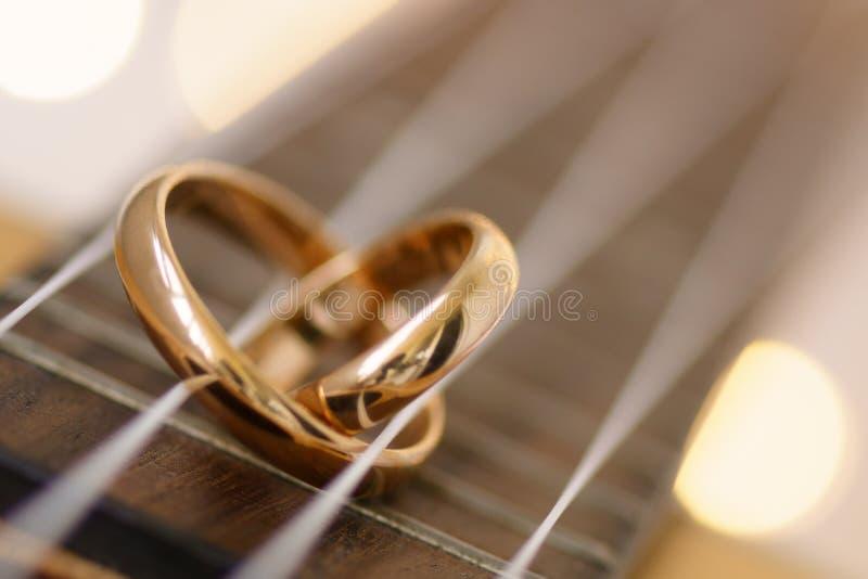 Obrączka ślubna w kierowym kształcie na ukulele gitarze zawiązuje fotografia royalty free