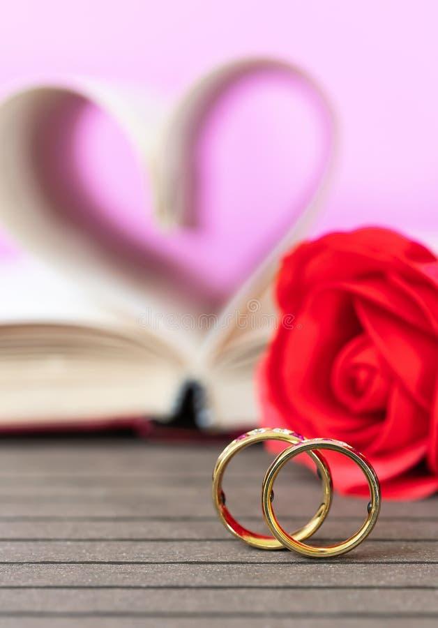 Obrączka ślubna z stronami książka wyginający się kierowy kształt z czerwieni różą obraz royalty free